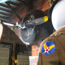 The empty gaze of a WW2 pilot's dress uniform gives the engine of the T6 trainer plane one last inspection.