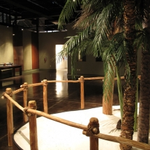 """The rustic cypress structures of the Calusa stand in stark contrast to the glossy wood finishes seen across the room in the """"soon to be built"""" exhibit featuring Spanish Exploration."""